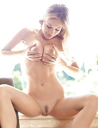 White t-shirt blond-haired beauty showing her trimmed pussy on a chair