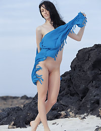 Flat-chested brunette posing completely naked on a rocky beach