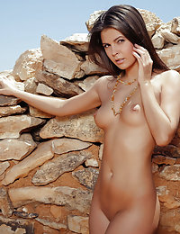 Tanned brunette is half-naked in a grey dress, among the ruins