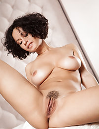 Curly-haired brunette in a white dress demonstrating her subtly hairy pussy