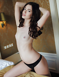 Wavy-haired beauty takes off her black lingerie on a king-sized bed