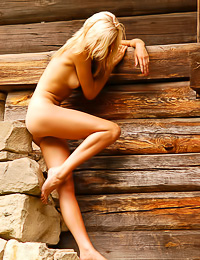 Attractive blonde bunny Olya A takes off her thongs outdoors by the cabin and shows her cunny.