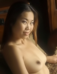 Arielle A: Hot Asian babe Arielle A poses nude on the bed and squeezes her firm round breasts passionately.