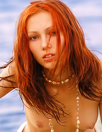 Foxy redhead chick Julia E takes off her white sheet and shows us her trimmed wet cunny.