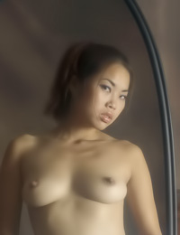 Seductive Asian model Arielle A takes her white shirt off and reveals her massive rack.