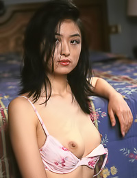 Foxy Asian beauty Yuka B takes off her panties and reveals her wet hairy bush on the bed.