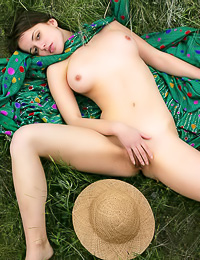 Horny teen babe Hilary A takes off her green dress on the field and plays with her hungry twat.
