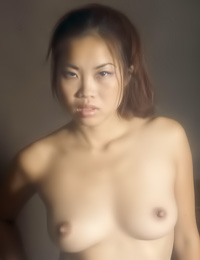 Erotic and exotic Asian girl takes off her night gown and poses in front of a big mirror.