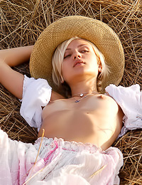 Foxy blonde babe Olya A takes off her white vintage dress outdoors on the green field.