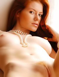 Beautiful redhead babe Tanya I strips in her room and shows us her perfect round breasts.