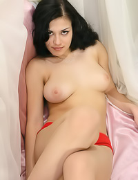 Busty brunette Irina C lies on the bed in her red panties and shows her big juicy breasts.