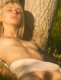 Seductive blonde angel Inna I takes off her white gown outdoors and shows her perky boobs.