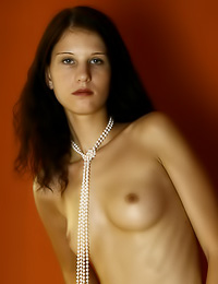 Skinny brunette looks best when having only pearl necklace on while posing for the camera.