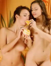 Horny lesbian models Hilary A and Lida A take off their clothes and eat oranges fully nude.