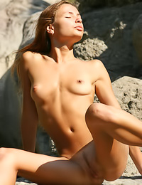 Horny Inna K oils her curvy hot body as she strips on the rocks and teases with her hooters.