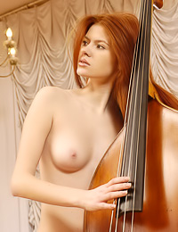 Red haired hottie likes nice music and enjoys posing naked with big music instruments.