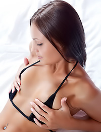 Taini A strips her sexy black lingerie set on the bed and plays with her hungry vagina.
