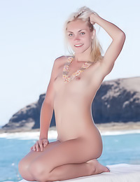 Cristina A: Naughty blonde chick poses nude on a bed flaunting her small boobs and her hairy snatch.