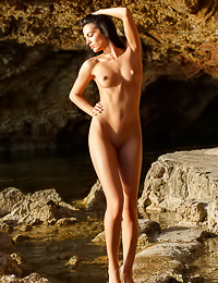 Sweet dark haired gal poses naked outdoors showing her perky tits and her sweet bald pussy.
