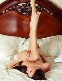 Yanika A: Smoking hot brunette poses naked on a bed showing her round perky tits and her bald snatch.