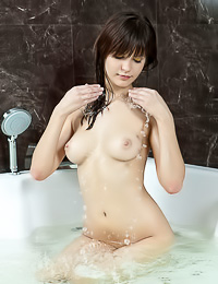 Alluring brunette tart poses naked in a bathtub flaunting her natural tits and her bald snatch.