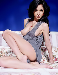 Stunning raven haired tart poses naked on a couch flaunting her natural boobs and her bald twat.