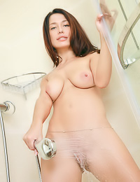 Dreamy brunette cutie poses naked in the shower flaunting her big tits and her firm booty.