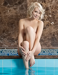 Feeona A: Mesmeric blonde cutie poses naked in a bathroom showing her small tits and her round ass.