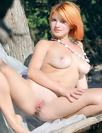 Red haired hottie shows off her naked body outdoors revealing her tits and her bald cunt.