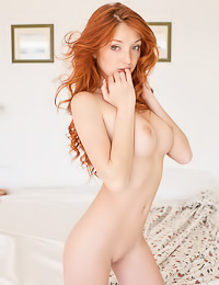 Tantalizing red haired beauty poses naked on a bed flaunting her big tits and her shaved cunt.