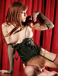 Big breasted redhead model Jade A takes her black corset off and shows her gaping shaved muff.