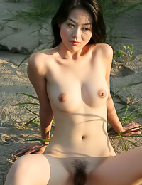 Lovely Asian babe Tiang Fang strips outdoors by the river and shows her hairy beaver.