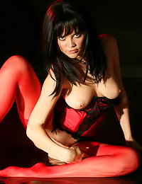 Fiery red girl with dark hair and lust to shame any porn star poses in erotic exotic poses.