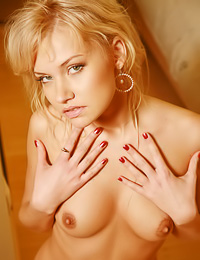 Busty blonde model Masha E takes her lingerie off on the bed and shows us her trimmed pussy.