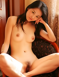 Busty Asian babe Tiang Fang strips completely naked and shows us how hairy her bush is.