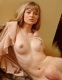 Lusty blonde model Julia Q takes off her sweater and reveals to us her big juicy breasts.