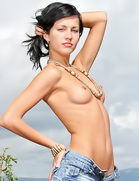 Sexy and seductive brunette Julia B takes off her denim clothes outdoors and shows her body.