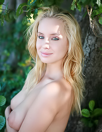 Dreamy blonde vixen Koika takes her clothes off in the woods and reveals her large nipples.