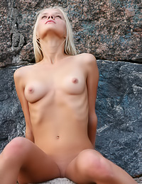 Attractive blonde bimbo Lisa B strips her bikini on the rocks and shows her natural nude body.