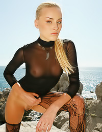 Small breasted blonde vixen Liza B takes off her lace top and teases us in black stockings.