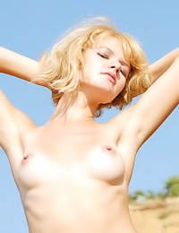 Smoking hot blonde model Dunya A strips her blue gown outdoors and shows her neat fanny.