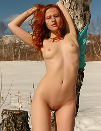 Nikol B: Lusty redhead model Nikol B takes off her blue gown and shows us her perky little tits.