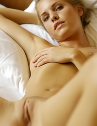 Beautiful and seductive blonde gal Iveta B poses nude on the bed and shows us her fanny.
