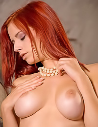 Beautiful and classy redhead chick Ariel A slowly takes off her skirt and shows us her butt.
