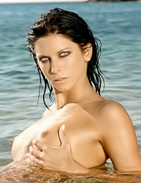 Foxy brunette model Kelly B strips her clothes on the beach and exposes her fresh fanny.