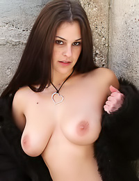 Big breasted brunette model Laila Lewis takes off her fur coat and exposes her massive hooters.