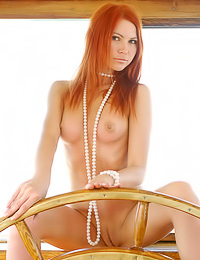 Smoking hot redhead gal Lidiya A takes off her bikini on a boat and exposes her fuckable body.