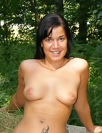 Busty brunette gal Stefanie A takes off her slutty clothes in the woods and shows off.