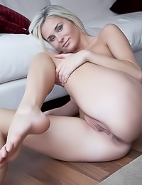 Beautiful blonde vixen Sonia C takes off her little black dress and shows us her shaved pussy.