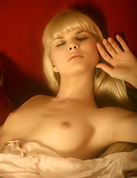 Dreamy and seductive blonde bunny Alicia A takes off her gown on the sofa and shows off.